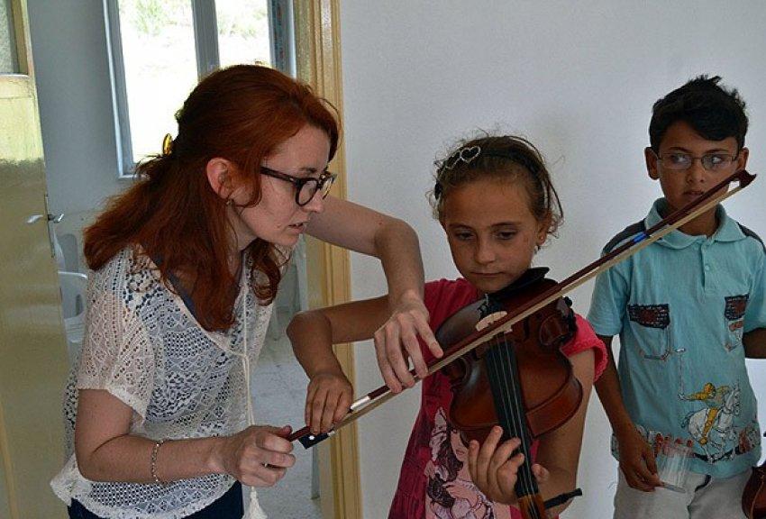 Köy çocuklarına keman öğretiyor